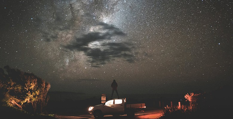 man standing on truck looking at the creation of the universe