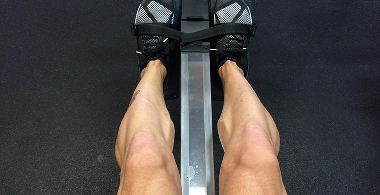Man flexing legs on rowing machine
