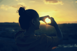 Woman creating heart shape with hands